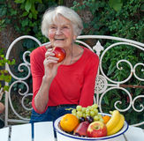 Happy Old Woman at the Garden Table with Fruits. Royalty Free Stock Photo