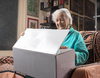 Happy old woman holding a large cardboard box. At home Royalty Free Stock Images