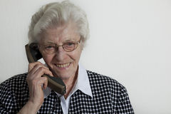 Happy old woman holding telephone Stock Image