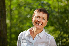 Happy old woman in nature Stock Photography