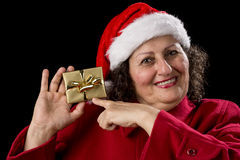 Happy Old Woman with Red Cap Points at Xmas Gift. Smiling gentle woman with red coat and Santa Claus cap isolated on black background. Pointing her left index Stock Image