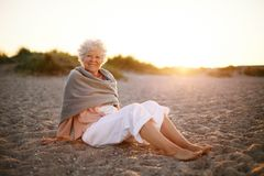 Happy old woman relaxing on the beach stock image