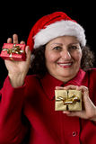 Happy Old Woman with Santa Hat and Two Xmas Gifts. Smiling elderly lady with red coat and Santa Claus hat is showing two small wrapped Christmas presents in her Royalty Free Stock Image
