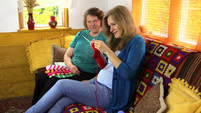 Happy old woman spend time knitting with pregnant granddaughter stock video footage