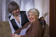 Happy old woman with woman. Happy old women with women at home Stock Photos