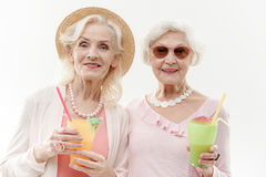 Happy old women having fun with exotic drink. Retirement is the best vacation. Portrait of joyful mature women standing and holding glasses of cocktails. They Royalty Free Stock Photos
