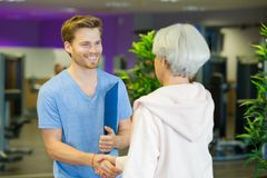 Happy old woman shaking hands with young male instructor. Happy old women shaking hands with her young male instructor Stock Photography