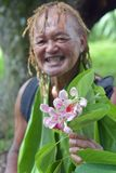 Happy Olde aged Pacific Islander man gives an exotic flower on e. Happy olde aged Pacific Islander man age 75 gives an exotic flower on eco tourism tour in stock photo