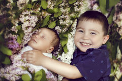 Happy older brother of three years, embracing his baby sister Royalty Free Stock Photo