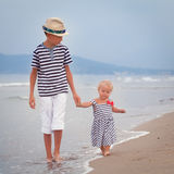 Happy older brother and younger cute sister walking on sea coast. Italy Royalty Free Stock Image