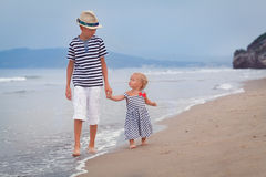 Happy older brother and younger cute sister walking on sea coast. Italy Stock Images