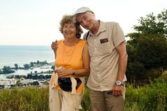 Happy Older Couple. Happy smiling older couple outdoor by a lake Stock Photo