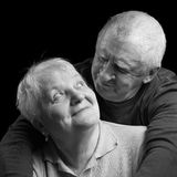 Happy older couple on a black background. A loving, handsome senior couple on a black background stock photo
