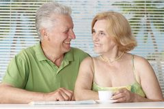 Happy older couple drink coffee stock image