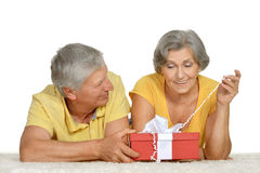 Happy older couple with gift Stock Images