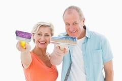Happy older couple holding paintbrushes Royalty Free Stock Images