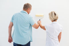 Happy older couple painting white wall Stock Photo