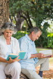 Happy older couple reading books together sitting on tree trunk Stock Photo