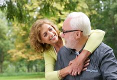 Happy older couple smiling and looking at each other outdoors royalty free stock images