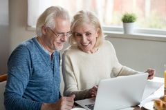 Happy older family couple talking using laptop having breakfast. Happy old family couple talking using laptop having breakfast together, surprised excited senior stock image
