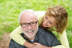 Happy older man with beautiful woman smiling outdoors. Close up portrait of a happy older men with beautiful women smiling outdoors royalty free stock images