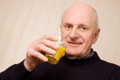 Happy older man with glass of juice. Happy senior older man holding a glass of fresh orange juice royalty free stock photos