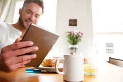 Happy older man with healthy breakfast holding tablet Royalty Free Stock Images
