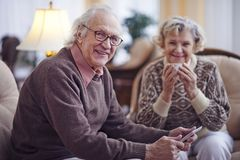 Happy older man. Senior men with touchpad looking at camera with his wife sitting on background royalty free stock image