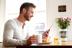 Happy older man with tablet drinking coffee with breakfast Stock Photos