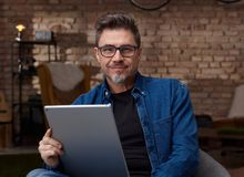 Older man sitting at home using tablet. Happy older white man with gray hair in casual jeans sitting at home using tablet, working Royalty Free Stock Images