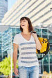 Happy older woman carrying duffel bag over shoulder Stock Photos