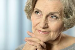 Happy older woman. Close-up portrait of a happy older woman on blue background Royalty Free Stock Image