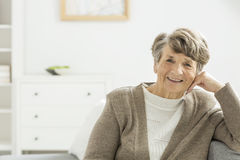Happy older woman. Happy older elegant woman sitting in a white nursing home stock photography
