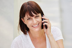Happy older woman holding mobile phone on call stock photos