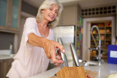 Happy older woman in kitchen with knife block Stock Photos
