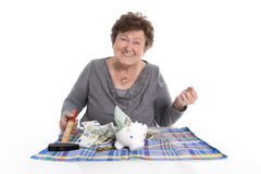 Happy older woman - rich person after smashing piggy bank. Money concept for pensioners stock image