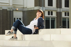 Happy older woman sitting on steps in city listening to music Stock Photo