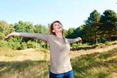 Happy older woman standing outside with arms outstretched royalty free stock photo