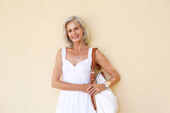 Happy older woman standing in white dress with purse Royalty Free Stock Images