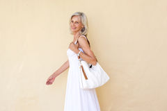 Happy older woman in summer dress walking with purse Royalty Free Stock Image