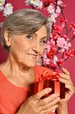 Happy olderly woman holding gift Stock Images