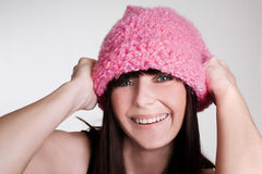 Happy one. Young woman playing with pink hat, smiling Stock Images