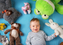 Happy one year old boy lying with many plush toys Royalty Free Stock Photography