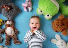 Happy one year old boy lying with many plush toys. On blue blanket Royalty Free Stock Image