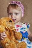Happy one year old girl playing and posing with a teddy bear royalty free stock image