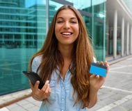 Happy online shopper holding smart phone and credit card looking at you in business district.  royalty free stock images