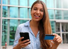 Happy online shopper holding smart phone and credit card looking at you in business district.  royalty free stock image