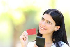 Happy online shopper showing card and looking at side. Happy online shopper holding smart phone showing blank credit card and looking at side in a park royalty free stock photography