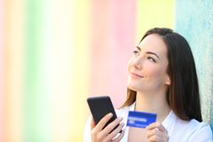Happy online shopper thinking looking at side royalty free stock image