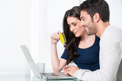 Happy online shopping. Smiling satisfied couple buying online with credit card at home